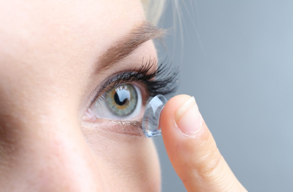 Woman putting in contact lens into her eye