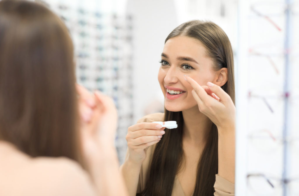 Young girl putting on contact lenses at optometrist office